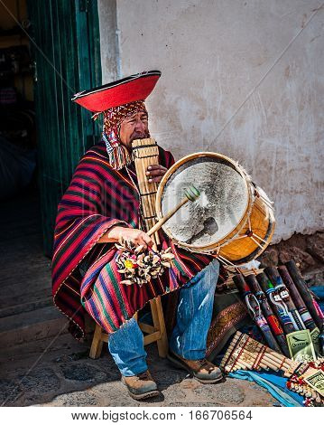 Cusco Peru - October 1 2016: Native Peruvian playing national musical instrument (Zampona Marimacha) dressed in colorful traditional native Peruvian closing.