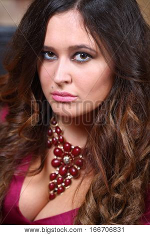 Portrait of beautiful woman with long hair in a magenta dress with a deep neckline and necklace