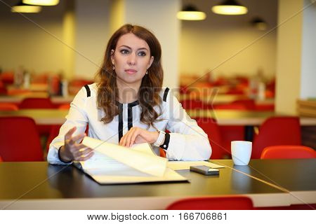 Young woman sitting at a table in front of an open folder in the canteen with tables and red chairs