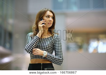 A young woman in a shortened top with long sleeves talking on mobile in the business center