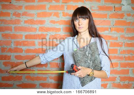 Woman with long hair with tape-measure in his hand near a brick wall on a construction site