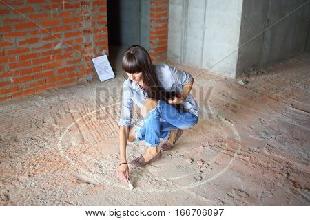 On the place of the future table woman draws a chalk circle on the floor in a newly built room