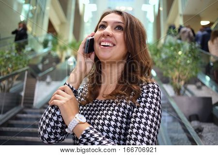 A young woman talking on mobile phone in front of the marble staircase of the business center