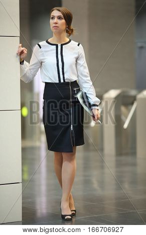 The woman in a white blouse and a black skirt with the folder standing in the lobby in front of turnstiles in business center
