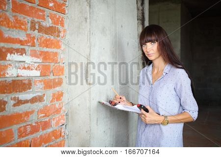 Woman with long hair standing near the concrete wall with the plan and pencil in hand on a construction site