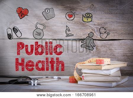 Public Health. Stack of books and a stethoscope on a wooden background.