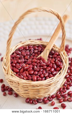 Raw adzuki red beans in woven basket on wooden background poster