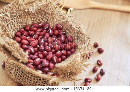 Raw adzuki red beans in small burlap bag on wooden background. Copy space