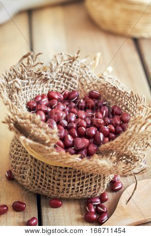 Raw adzuki red beans in small burlap bag on wooden background