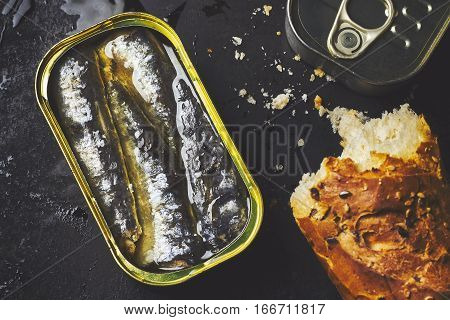 Sardines in a can with loaf of bread on black rustic background. Top view