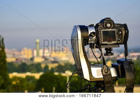 Camera fixed on automatic panorama head with out of focus city in background