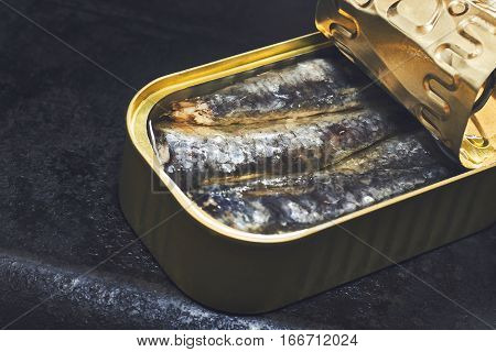 Sardines in a can on black rustic background