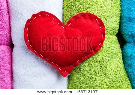 Red homemade heart on colorful towels on Valentine's Day. Romantic spa abstract concept.