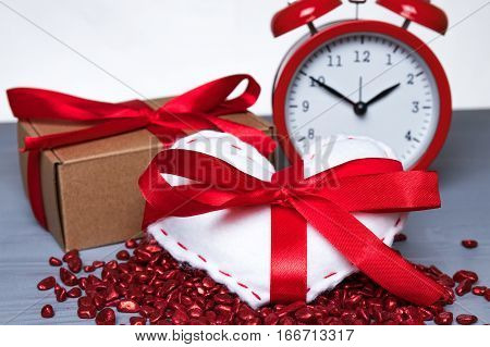 White homemade heart with red ribbon bow with present or gift and a vintage clock on Valentine's Day. Time for love or romance abstract concept.
