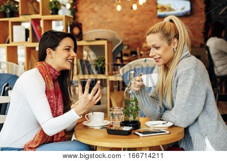 Two women drinking coffee in a cafe talking and looking at the phone
