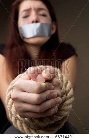 Unhappy brunette with hands tied