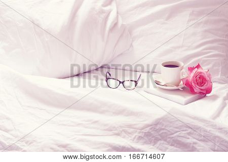 Open white, rumpled bedding with coffee, book, eyeglasses and flower. Room for copy.