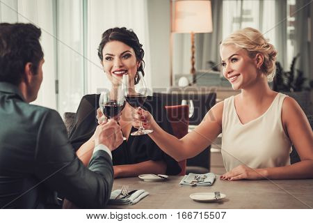 Group of elegant people clinking glasses of red wine in restaurante