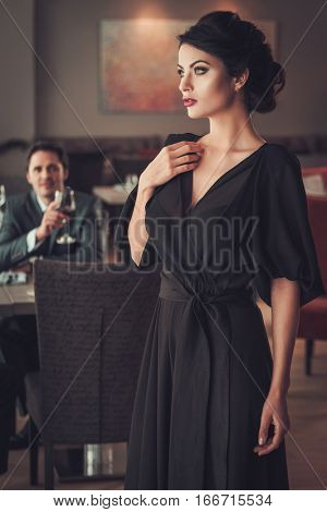 Elegant brunette lady in black evening dress in restaurant