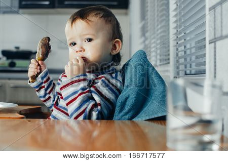 The child greedily eating chicken fatty and delicious in the kitchen very hungry
