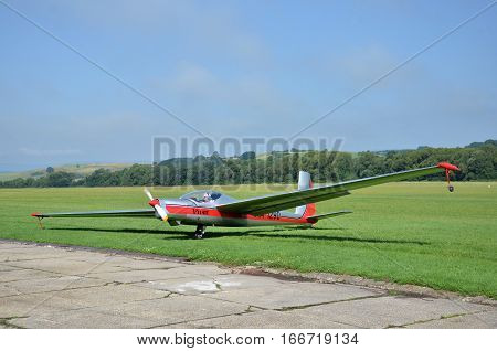 Ocova Slovakia - August 2 2014: Silver and red glider stands on grass landing strip in small country airport while the weather is nice