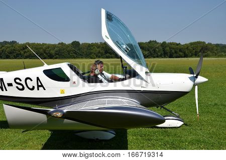 Ocova Slovakia - August 2 2014: Two men sit into ultralight propeller-driven airplane and get ready for taking off