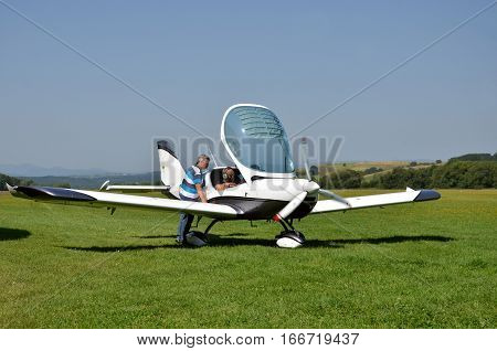 Ocova Slovakia - August 2 2014: Men check the small personal airplane before taking off and prepare for the flight next to grass landing strip
