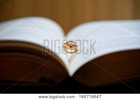 Wedding rings on a book in beautiful day