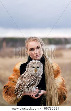 Beautiful woman in a fur coat with an owl on his arm. Blonde with long hair in nature holding a owl. Romantic delicate image of a girl