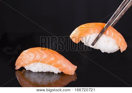 One sushi with salmon on a black background