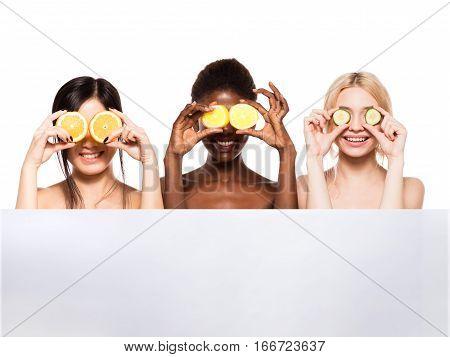Three Different Ethnic Women With Lemon, Orange And Cucumber