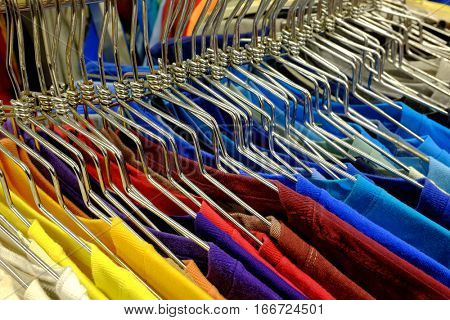 Colored shirts on hangers set on a rack to sell in the store