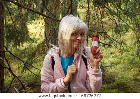 A female geocacher in a forest holding a container