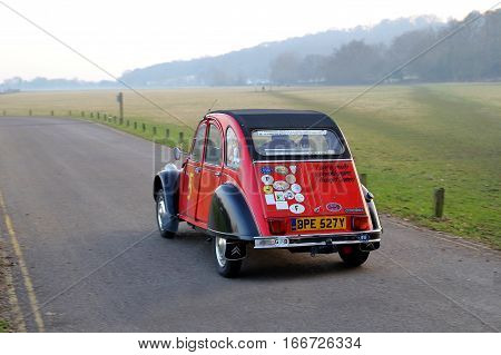 Runnymede Surrey UK - Jan 22 2017: A Citroen 2CV (Deux Chevaux) in red decorated with stickers from rallies and races driving through misty countryside.