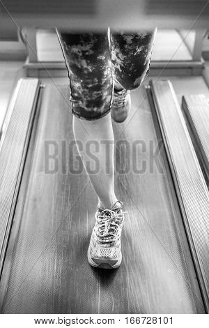 Close up of woman feet in colorful shoes running on treadmill machine indoor. Fitness center training. Healthy lifestyle concept. Black and white shot.