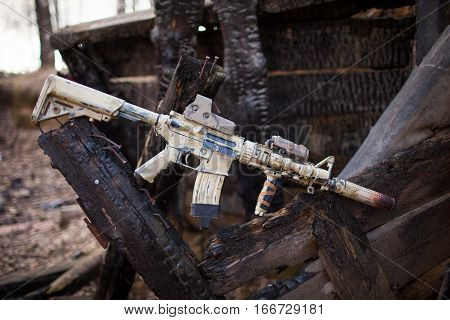 Assault Rifle, painted in sand color on the background of the burnt logs. Airsoft.