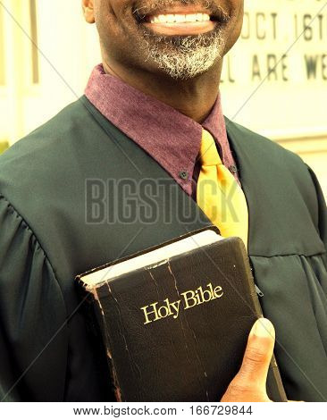 Portrait of happy preacher holding Holy Bible while standing in front of church