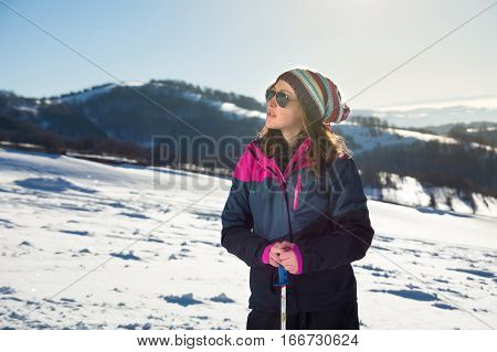 Woman With Hiking Sticks Standing On The Mountain Top