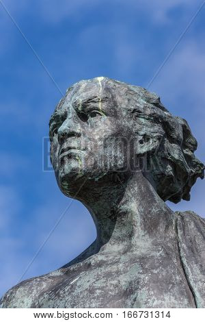 Helmsdale Scotland - June 4 2012: The Emigrant Statue at the south entrance of the town. Closeup of head of adult male. Blue sky bronze with green spots.