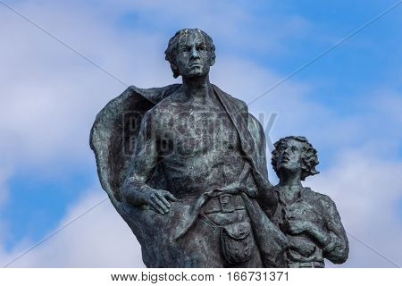Helmsdale Scotland - June 4 2012: The Emigrant Statue at the south entrance of the town. Closeup of upper body of adult male and his son. Blue sky with faint white clouds bronze with green spots.