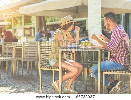 Happy couple eating piadina sandwich and toasting beer in bar kiosk restaurant. Young people having fast meal sitting outdoor - Relationship concept - Focus on girl face - Warm cinematic filter