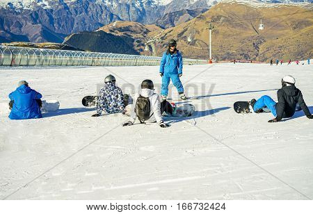 Snowboarder instructor teaching apprentice learners special tricks and performances - People learning at ski school in mountains vacation - Winter sport concept - Focus on teacher - Warm filter