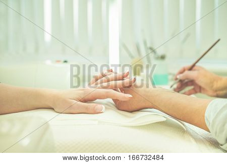 Woman doing manicure treatment to customer girl in beauty shop - Manicurist painting nails with gel liquid - Body care and fingernail concept - Focus on left female hand - Warm cinematic filter