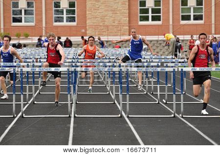 Teen Boys Competing In High School Hurdles Race