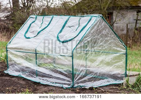 Mini greenhouse for growing seedlings is covered with plastic installed in the vegetable garden in early spring