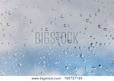 Raindrops on window glass against blue sky with white clouds