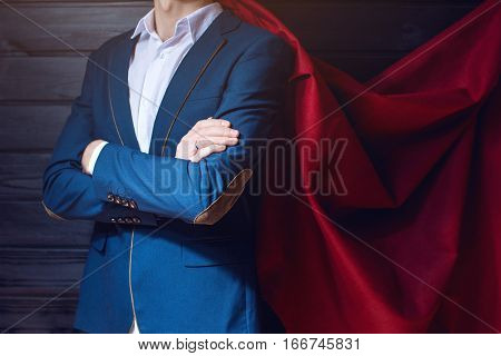 Businessman standing in a suit and red cloak like a superhero on a dark background. the concept of progress in your career