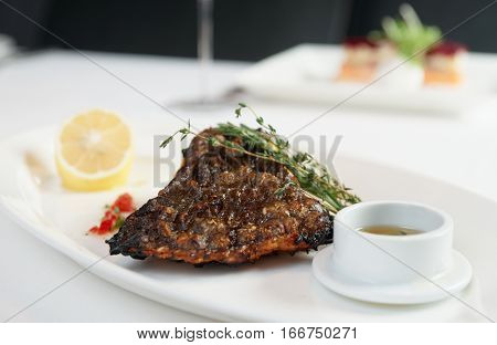 Grilled flounder with lemon and savory sauce in gravy boat, restaurant dish