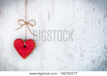 Valentines day concept. Heart shaped cookie tied with hemp bow over white wood rustic background.