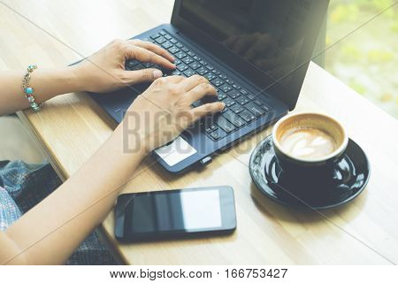 Businesswoman working with modern devices laptop computer and mobile phone in coffee shopwoman's hands using smart phone in interior woman at her workplace using technology .
